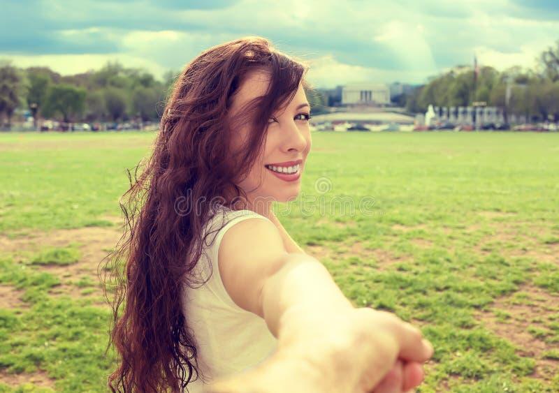 Femme heureuse dans le Washington DC du centre vous prolongeant un bras invitant à rendre visite à Lincoln Memorial photographie stock
