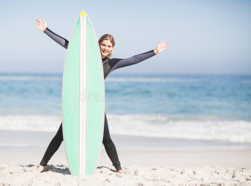 Femme heureuse dans le wetsuit avec la planche de surf sur la plage photo stock