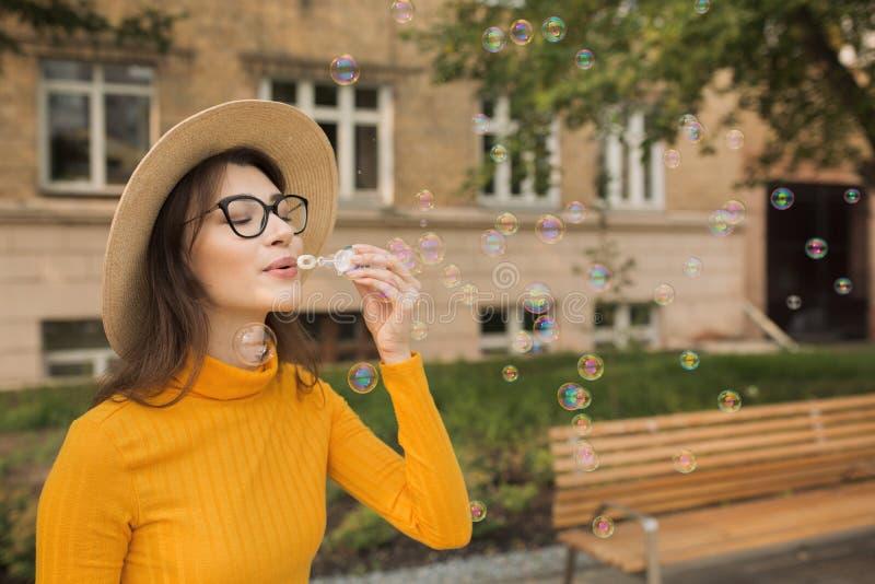 Femme heureuse dans les bulles de savon de soufflement de ville photos libres de droits