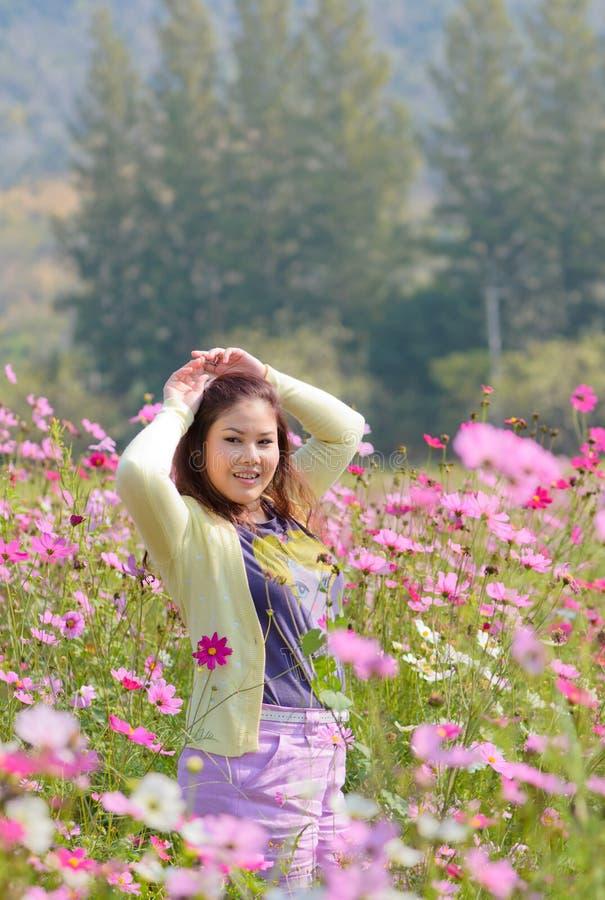 Femme heureuse dans un beau domaine de fleur. photographie stock