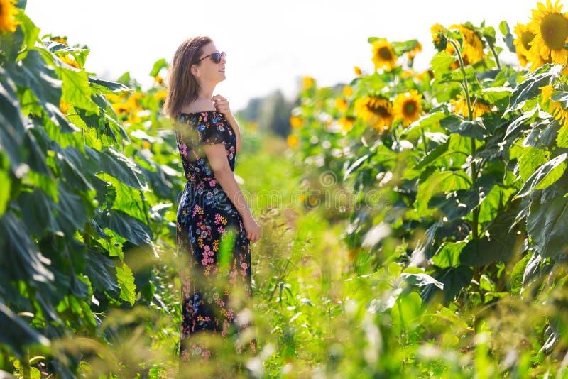 Femme heureuse dans un domaine des tournesols photographie stock