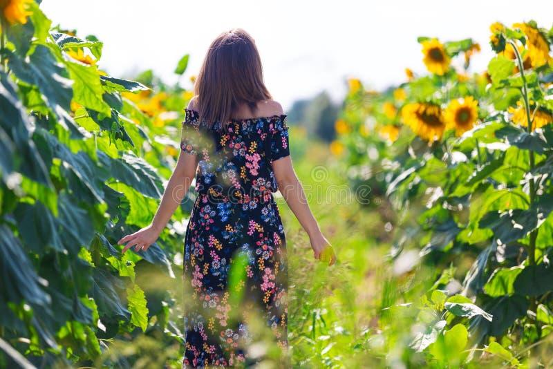 Femme heureuse dans une robe florale dans un domaine des tournesols photos stock