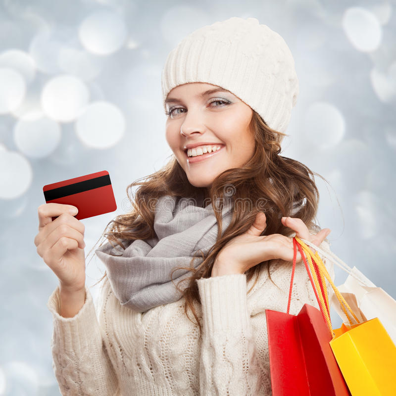 Femme heureuse de achat tenant les sacs et la carte de crédit Ventes d'hiver photo stock