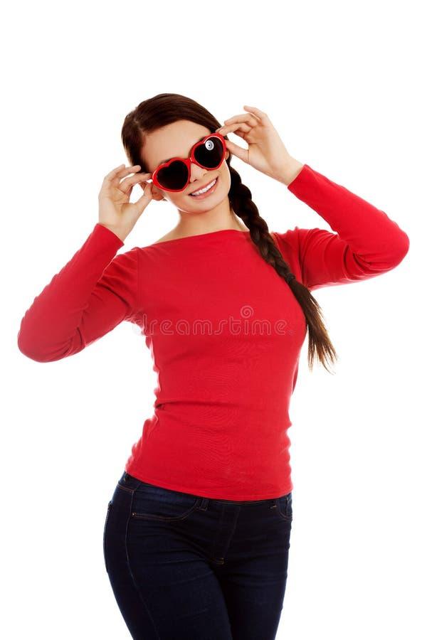 Femme heureuse de brune avec des lunettes de soleil sous forme de coeurs photos stock