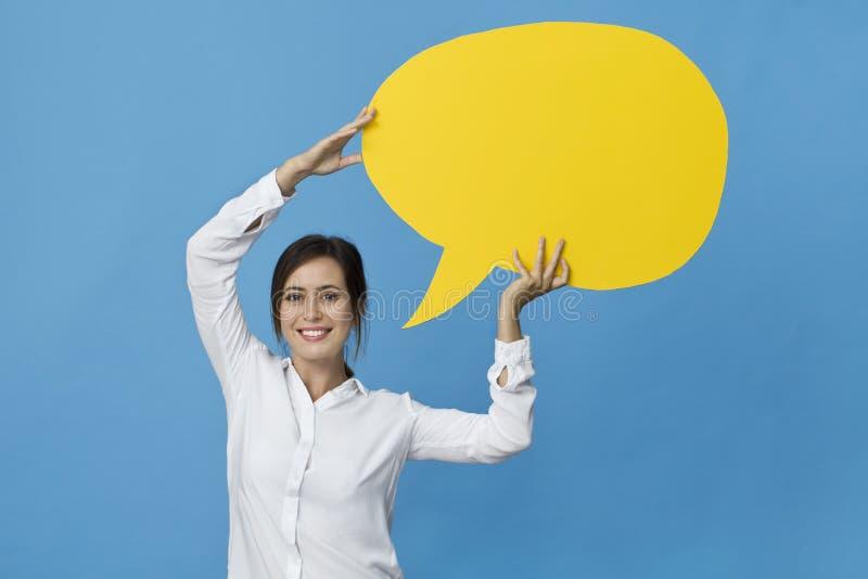 Femme heureuse de brune dans la chemise blanche élégante avec la bulle jaune de la parole sur le fond bleu photo stock
