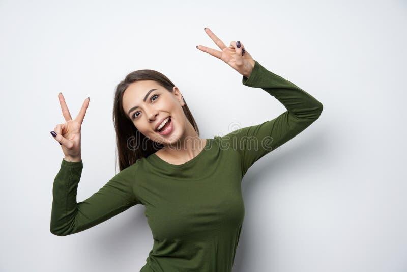 Femme heureuse de brune faisant des gestes le sourire de signe de paix photographie stock libre de droits