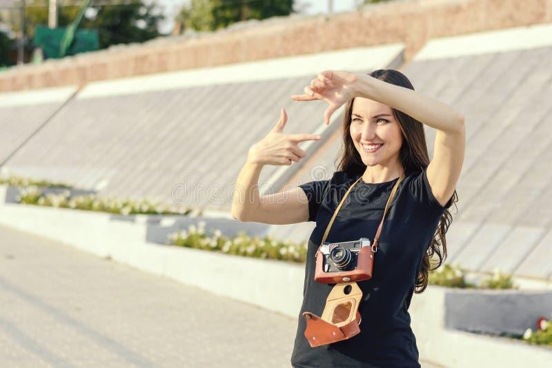 Femme heureuse de brune faisant la photo avec le rétro appareil-photo sur la rue de ville image libre de droits
