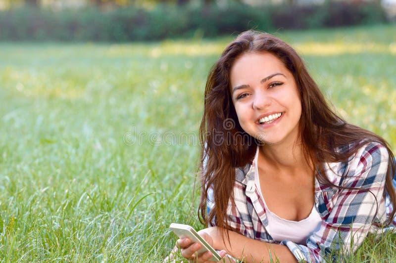 Femme heureuse de brune se trouvant sur l'herbe en parc avec le smartphone image libre de droits