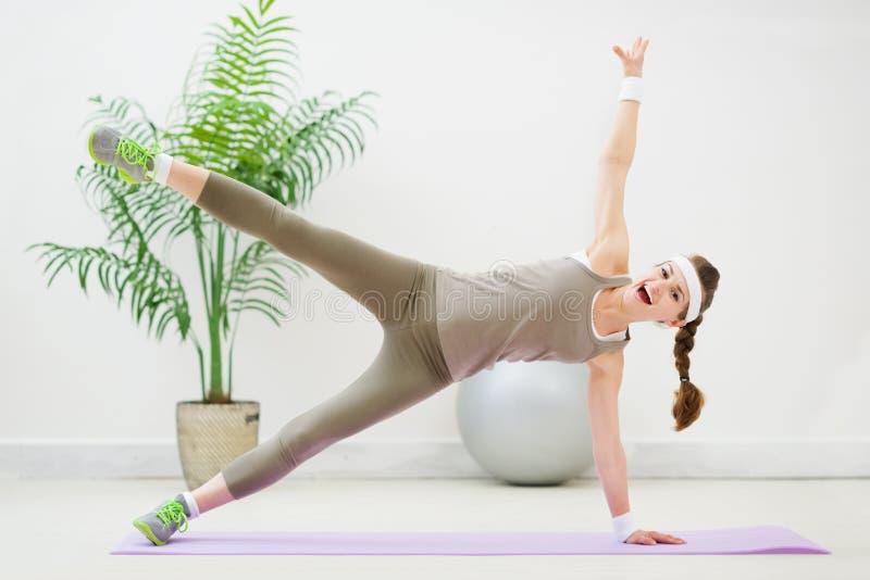Femme heureuse de forme physique effectuant la gymnastique sur l'étage images libres de droits