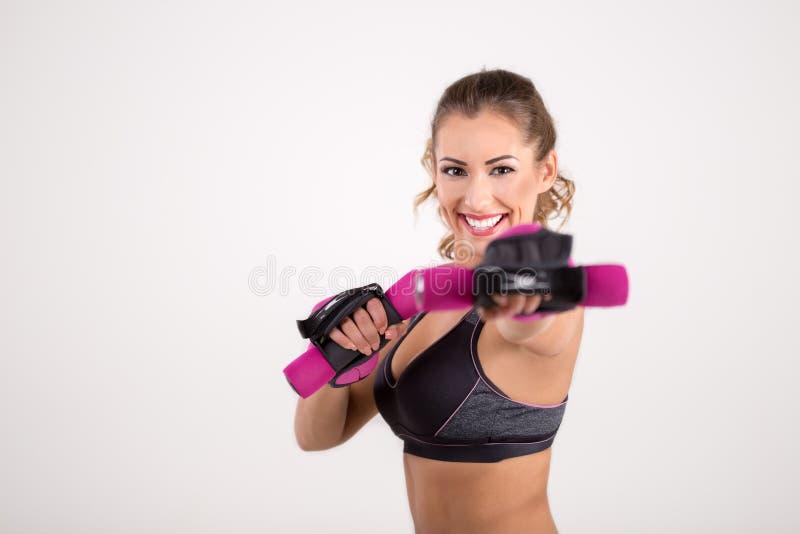 Femme heureuse de forme physique tenant des haltères et le sourire images stock