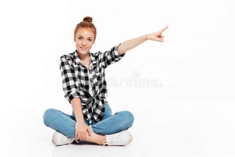 Femme heureuse de gingembre dans la chemise et des jeans se reposant sur le plancher image libre de droits