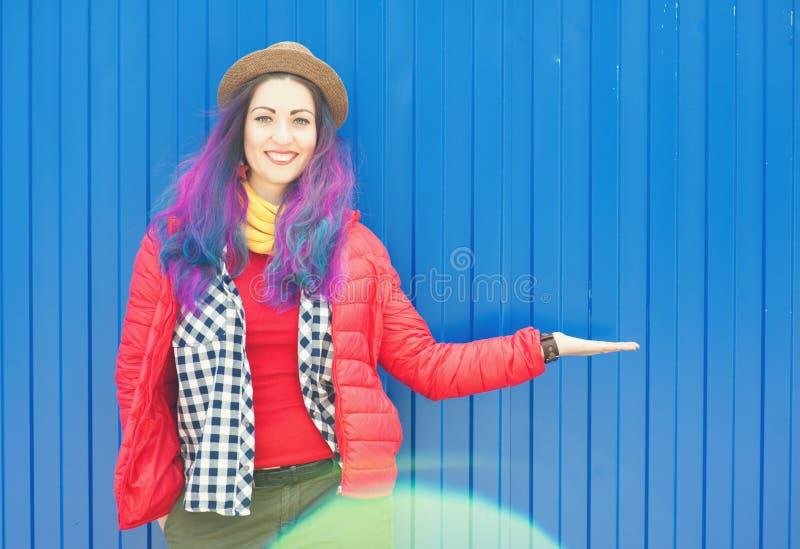 Femme heureuse de hippie avec les cheveux colorés montrant quelque chose en main images libres de droits