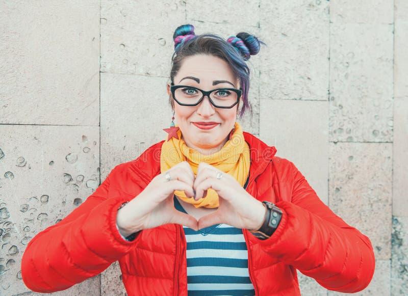 Femme heureuse de hippie de mode avec les cheveux colorés montrant le coeur par photo stock
