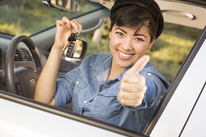 Femme heureuse de métis dans la voiture tenant des clés photo stock
