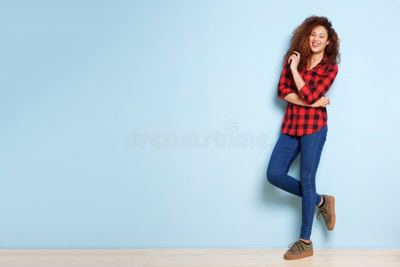 Femme heureuse de plein corps avec les cheveux bouclés se penchant sur le fond bleu images libres de droits
