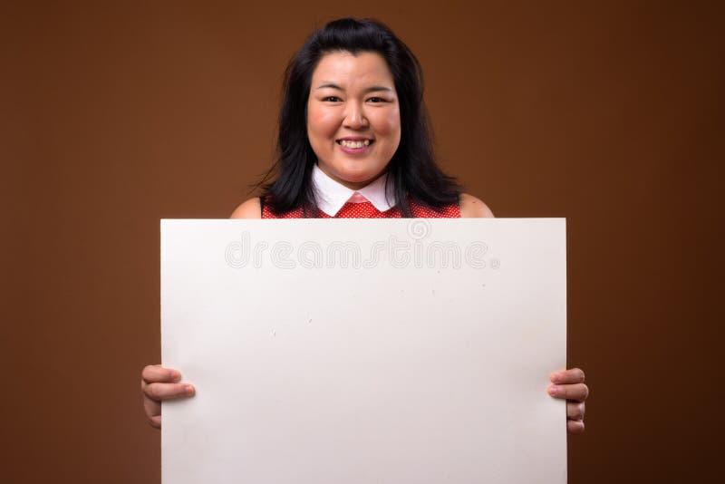Femme heureuse de poids excessif tenant le conseil blanc vide avec l'espace de copie image stock