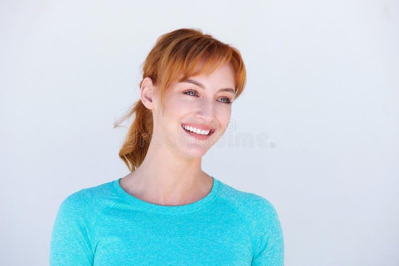 Femme heureuse de roux souriant par le mur blanc photographie stock libre de droits