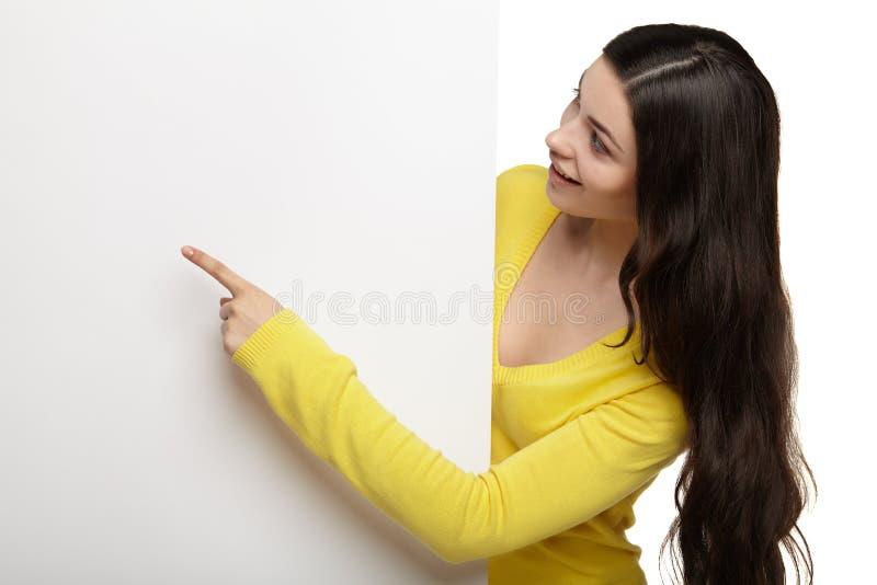 Femme heureuse de sourire dirigeant son doigt au conseil image libre de droits