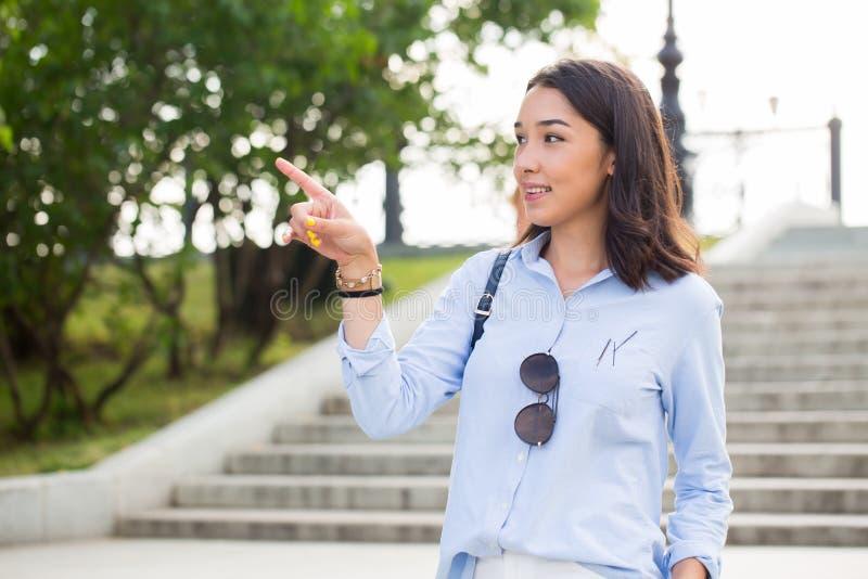 Femme heureuse de sourire indiquant le doigt le côté avec une expression espiègle images stock