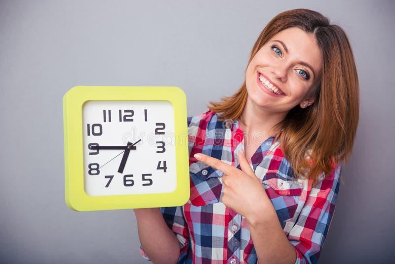 Femme heureuse dirigeant le doigt sur l'horloge photographie stock
