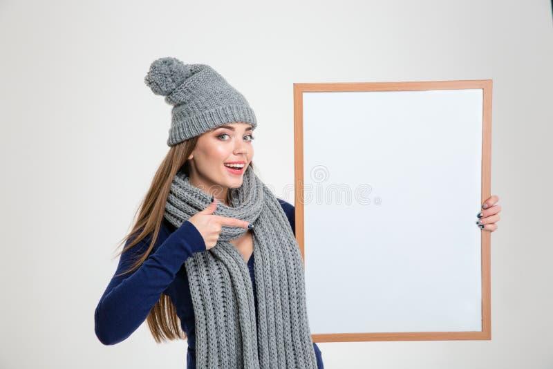 Femme heureuse dirigeant le doigt sur le conseil vide photos stock