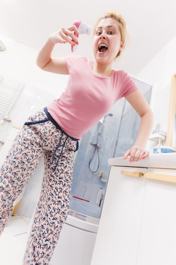 Femme heureuse employant la brosse de nettoyage faciale images libres de droits