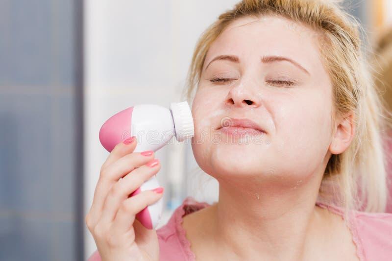 Femme heureuse employant la brosse de nettoyage faciale image stock
