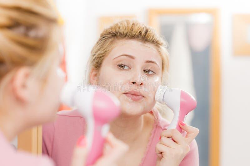 Femme heureuse employant la brosse de nettoyage faciale photographie stock libre de droits