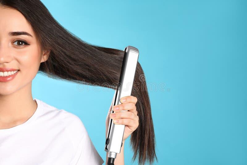 Femme heureuse employant le fer de cheveux L'espace pour le texte image libre de droits