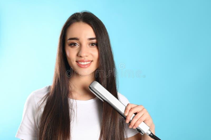 Femme heureuse employant le fer de cheveux sur le fond de couleur photo libre de droits