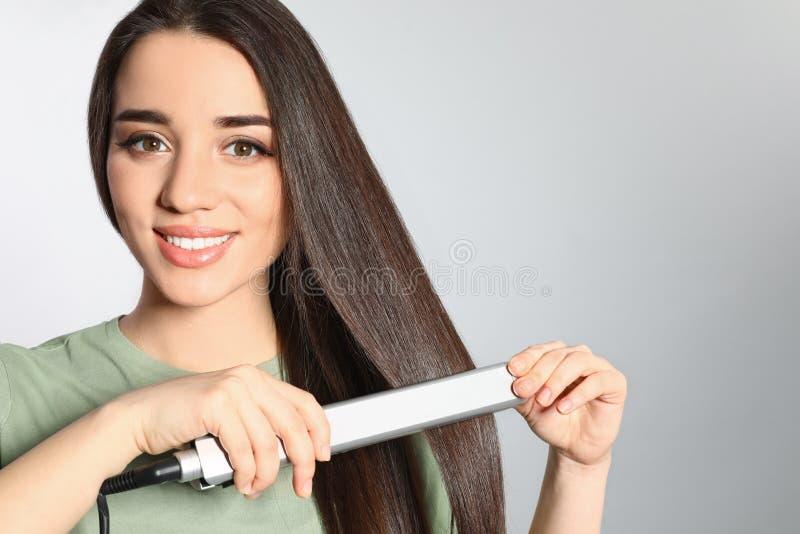 Femme heureuse employant le fer de cheveux sur le fond gris image libre de droits