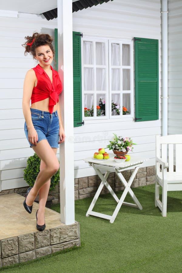 Femme heureuse en bref maison de campagne de poses la prochaine images stock
