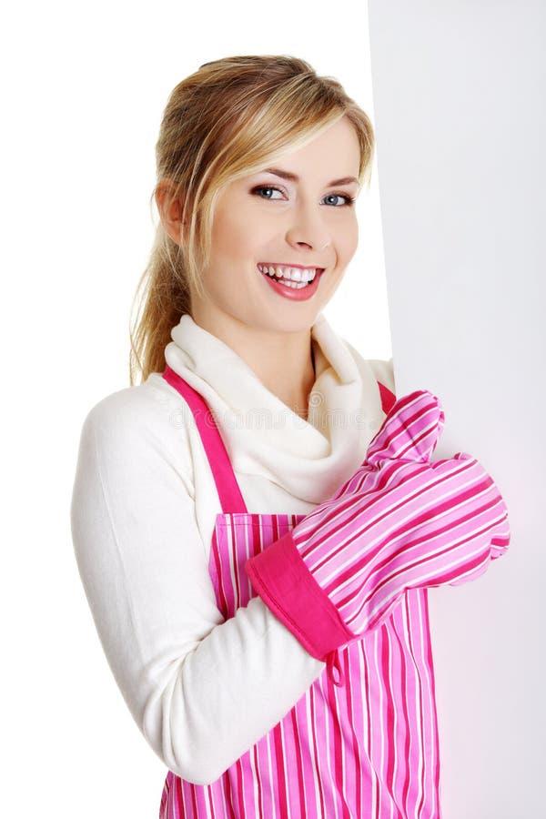 Femme heureuse en panneau-réclame rose de signe de fixation d'appron. photo libre de droits