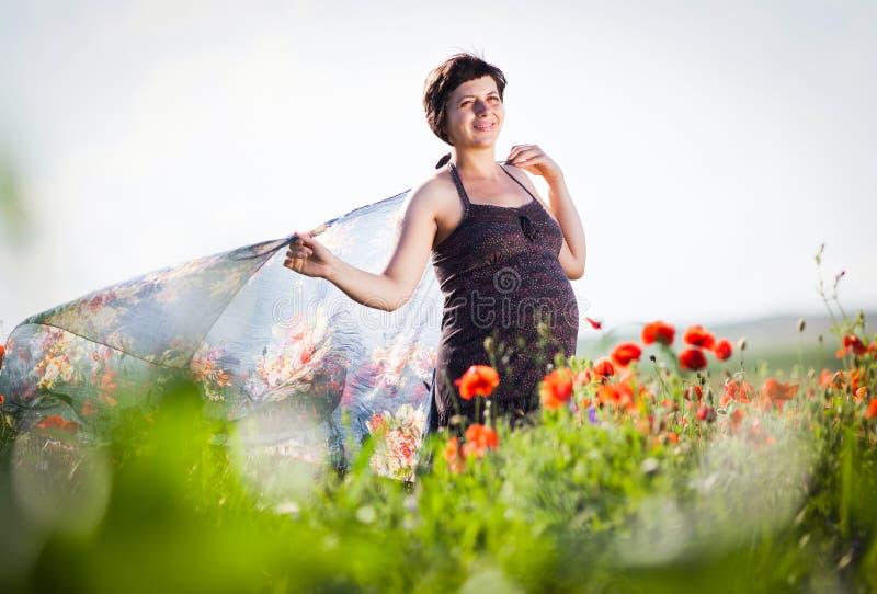 Femme heureuse enceinte dans un domaine fleurissant de pavot image libre de droits