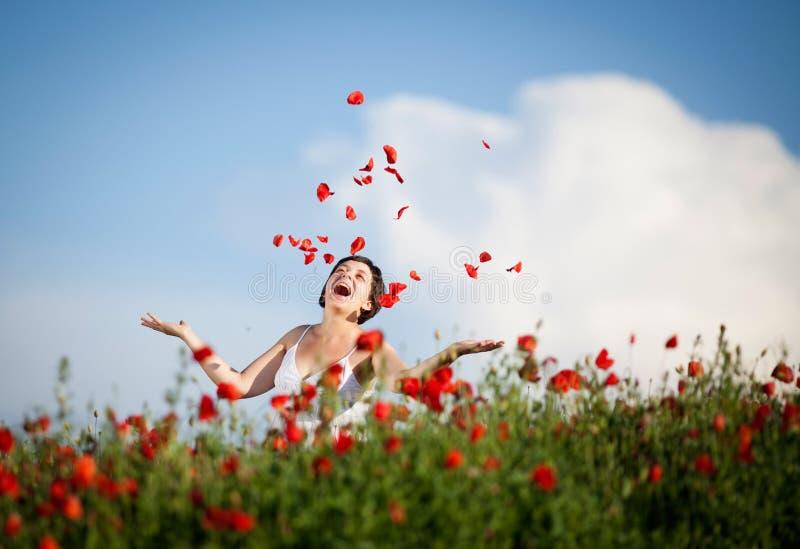 Femme heureuse enceinte dans un domaine fleurissant de pavot image stock
