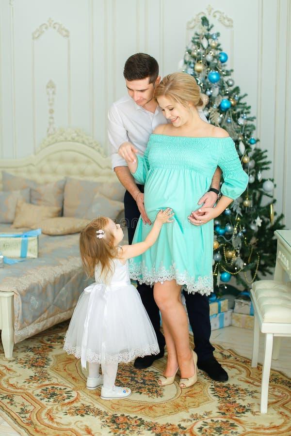 Femme heureuse enceinte portant la robe bleue se tenant avec le mari et la petite fille près de l'arbre de Noël photographie stock