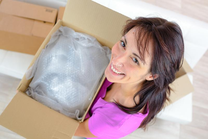 Femme heureuse entrant dans les boîtes de transport de cartons de nouvel appartement images stock