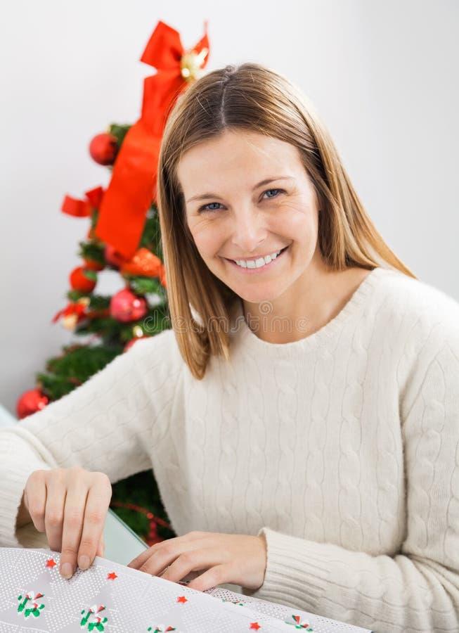Femme heureuse enveloppant le cadeau de Noël photo libre de droits