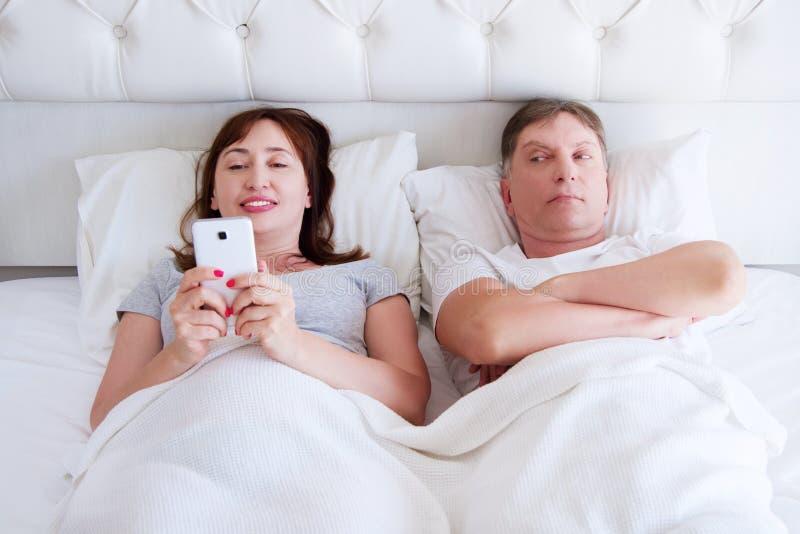 Femme heureuse et homme malheureux dans la chambre à coucher, couple de Moyen Âge, problème de famille photographie stock