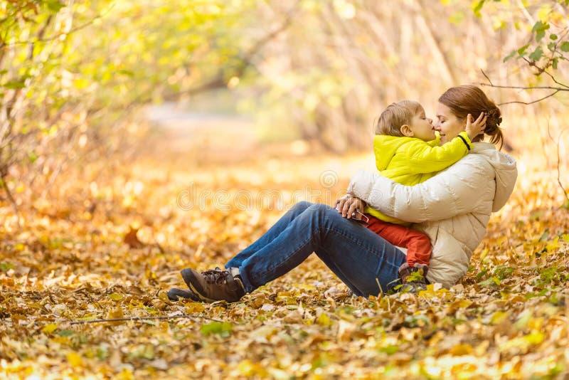 Femme heureuse et son petit fils ayant l'amusement dans un parc d'automne image stock