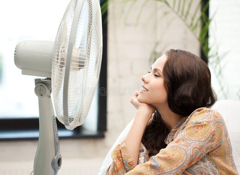 Femme heureuse et souriante s'asseyant près du ventilateur images stock