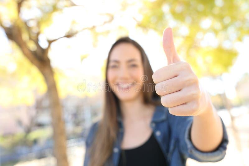 Femme heureuse faisant des gestes le pouce en parc photos libres de droits