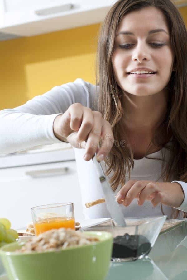Femme heureuse faisant le déjeuner photographie stock libre de droits