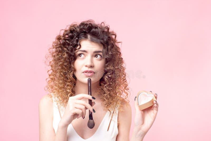 Femme heureuse gaie s'asseyant avec une brosse de maquillage tout en travaillant dans le salon de beaut? photo stock