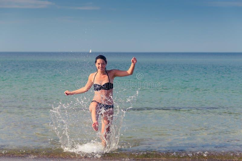 Femme heureuse gambadant sur une plage tropicale images stock