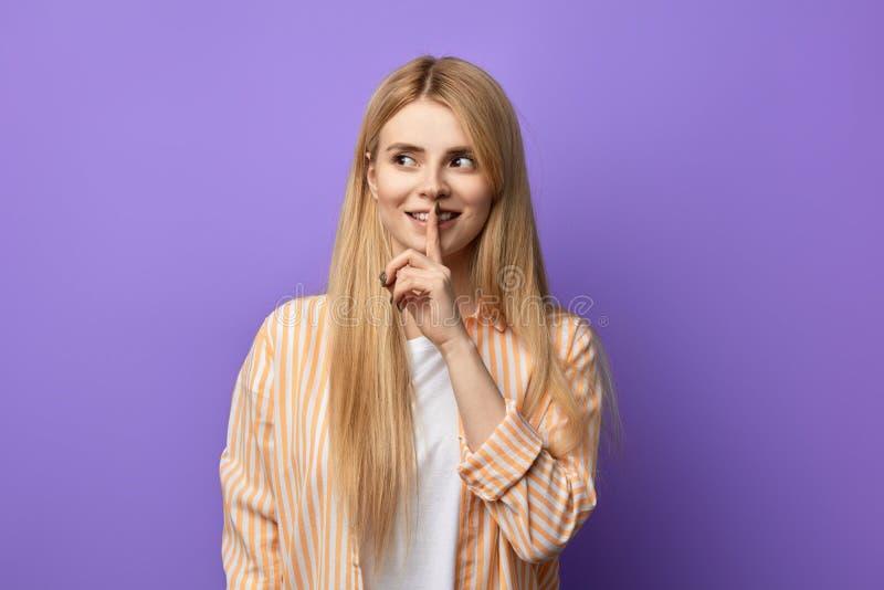 Femme heureuse impressionnante attirante avec le doigt sur ses lèvres image stock