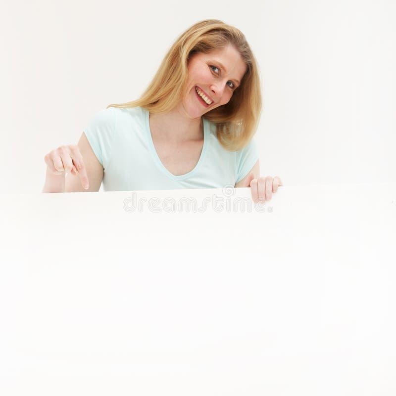 Femme heureuse indiquant un panneau blanc photo stock