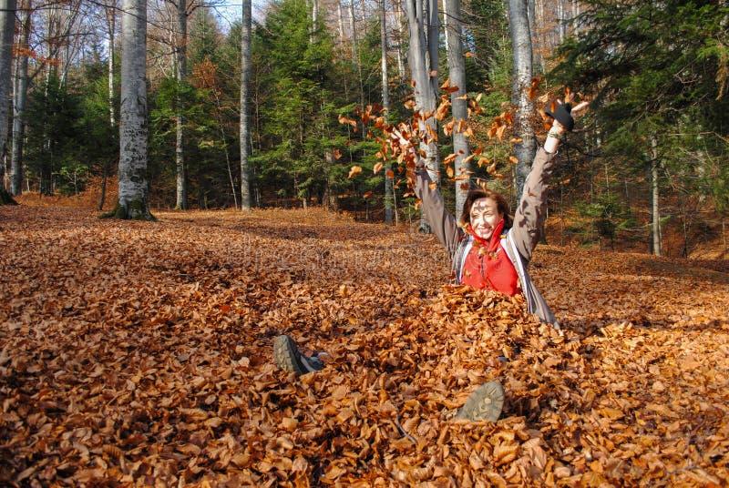 Femme heureuse jouant avec des feuilles d'automne photo stock