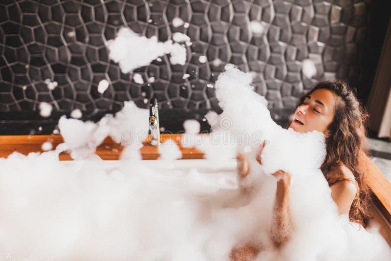 Femme heureuse jouant avec la mousse dans le grand bain dans la station thermale images libres de droits