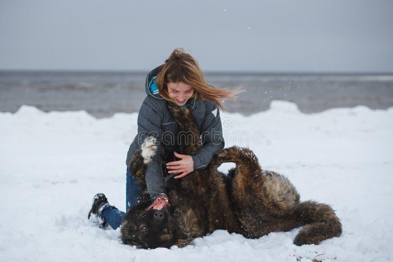 Femme heureuse jouant avec son chien sur la plage de mer d'hiver image libre de droits